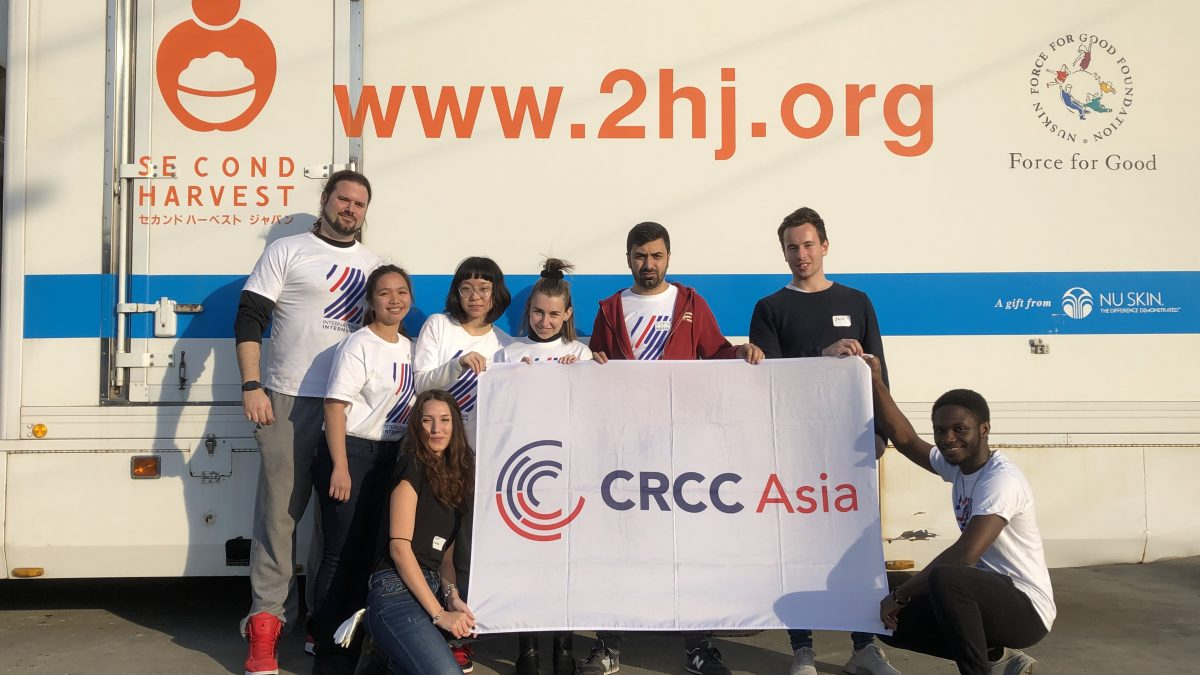 CRCC Asia Tokyo interns stand with the company flag outside of the Second Harvest food bank