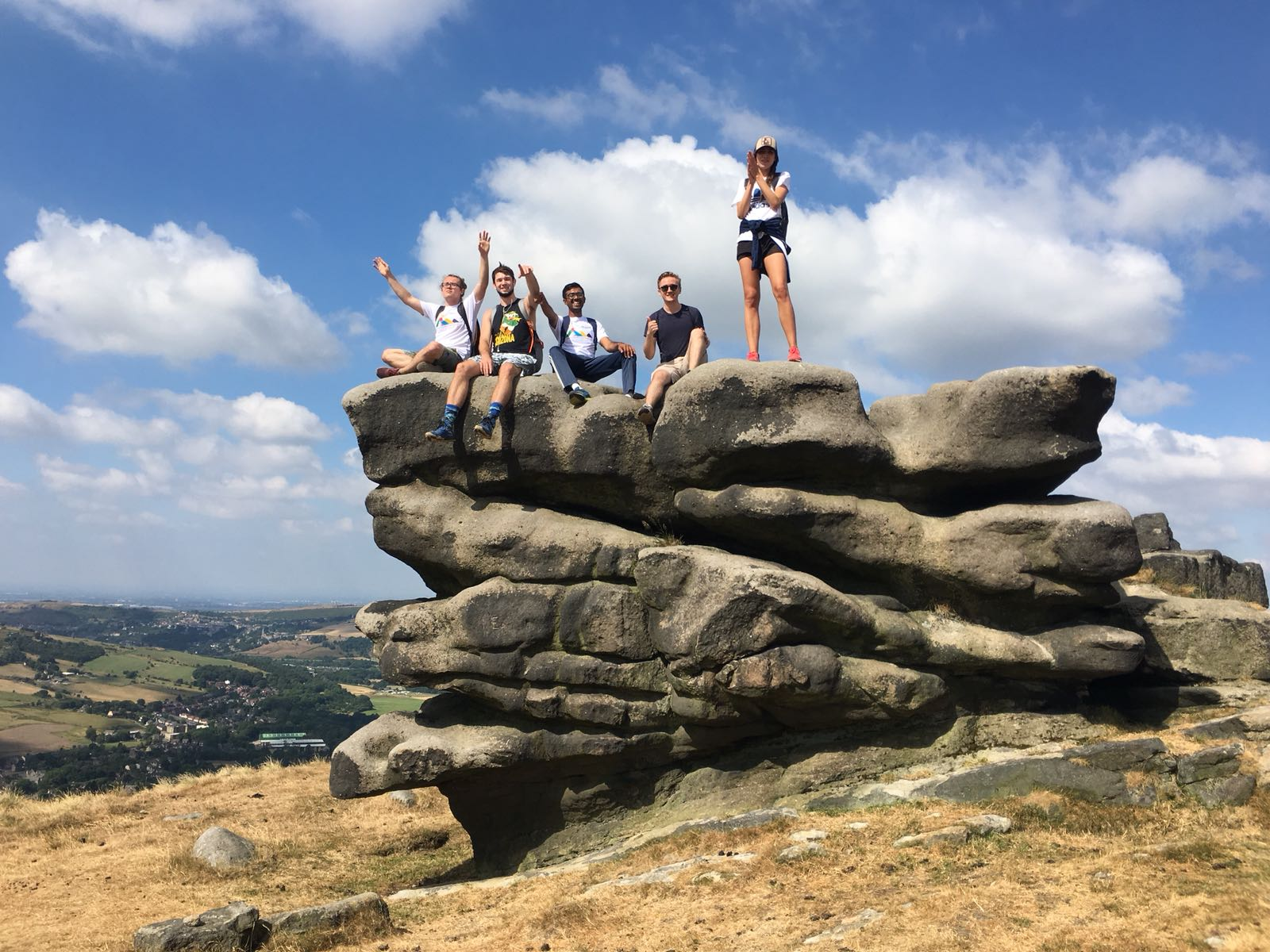CRCC Asia interns stand atop a rock in the hills of the Peak District near Manchester