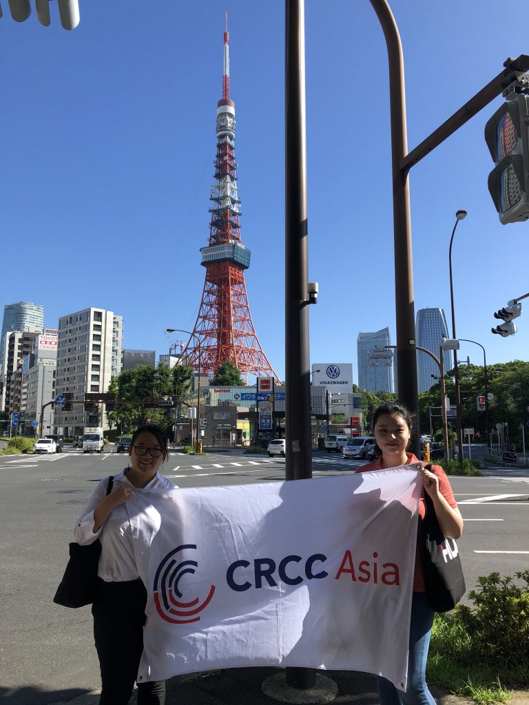 How to Get a Job in Japan - Two interns hold the CRCC Asia flag in front of Tokyo Tower