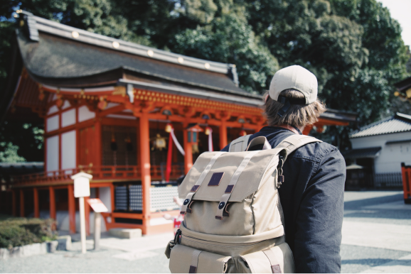flights and travel insurance man wearing a backpack looking at a shrine in Japan