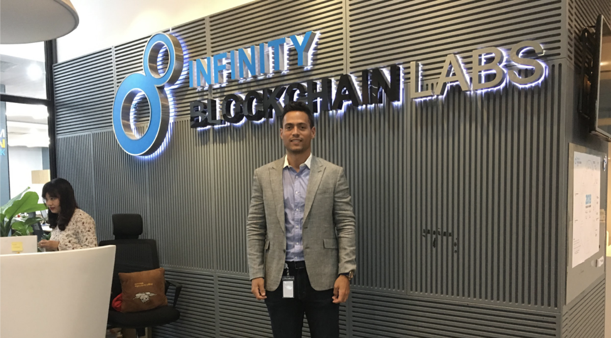 Carloz Marquez standing at reception desk of Infinity Blockchain Labs on his Blockchain Internship with CRCC Asia